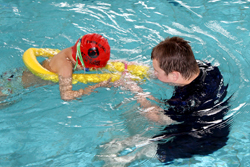 Student swimming with instructor