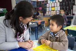 Preschool student and preschool assistant talking